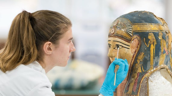 Student dusting off a sarcophagus