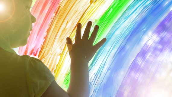A young child puts their hand on a rainbow painted on a window.