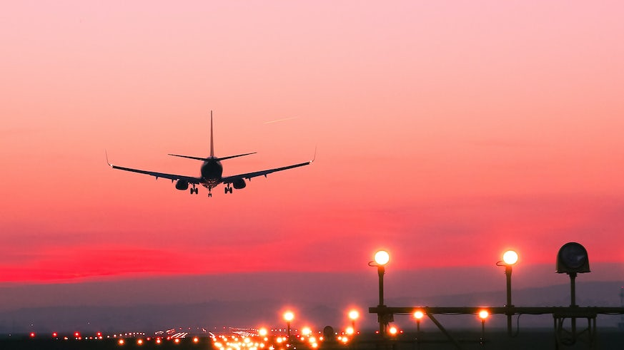 Stock image of plane flying into the sunset