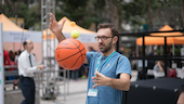Dr Gomez demonstrating with a basketball for a physics lesson