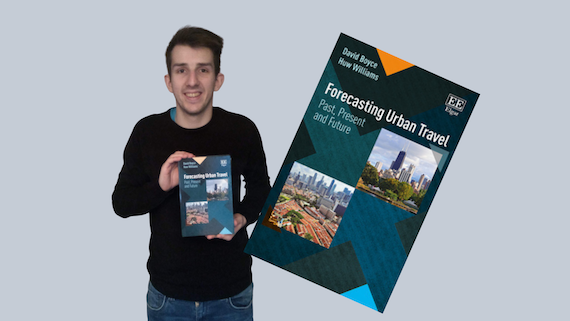 Picture of young male graduate wearing jeans and a jumper holding a copy of the book he won in front of him