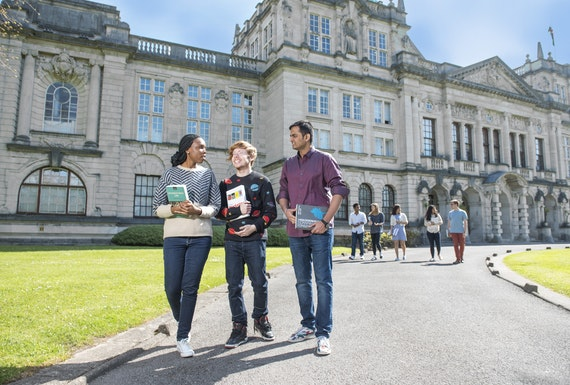 Three students outside the university talking and carrying books