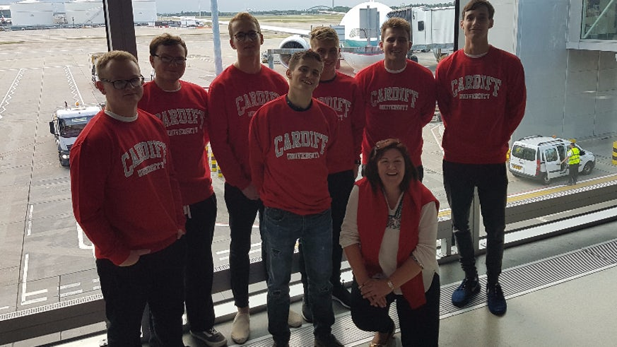 Image of seven male students and Dr Jane Lynch at Heathrow Airport