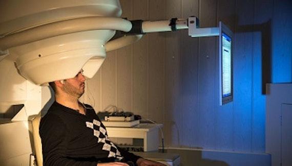 Man sitting in a MEG scanner