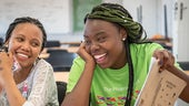 Namibian girl with green braids holding an exercise book and laughing with another girl