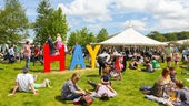 Image of a busy Hay Festival field, with HAY in large free standing letters.