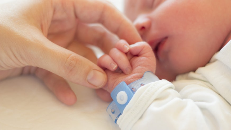 Image of a baby with the mother's hand holding its hand
