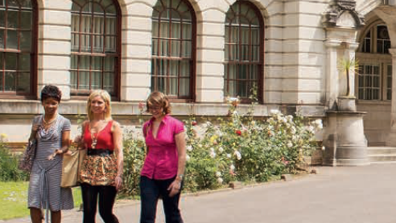 Image of three women walking in front of the main Cardiff University building.