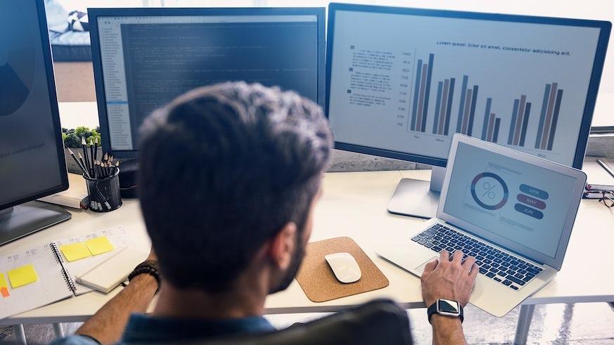 A man at a computer looking at data charts