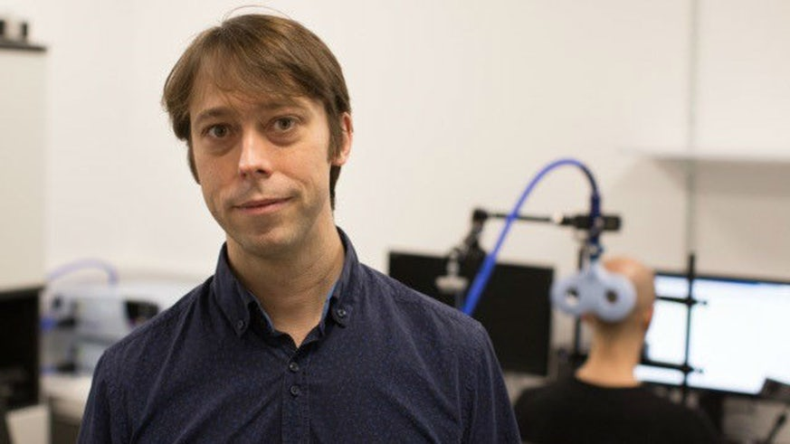Picture of a CUBRIC research fellow with a blurred background of a participant receiving brain stimulation