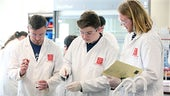 Three students taking part in a lab experiment