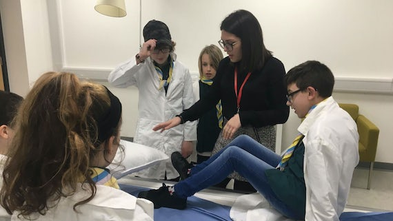 a female researcher shows scouts how to do an mri scan