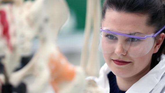 Female student looking at skeleton