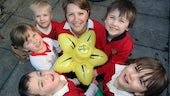 Lady and five children holding an inflatable daffodil.