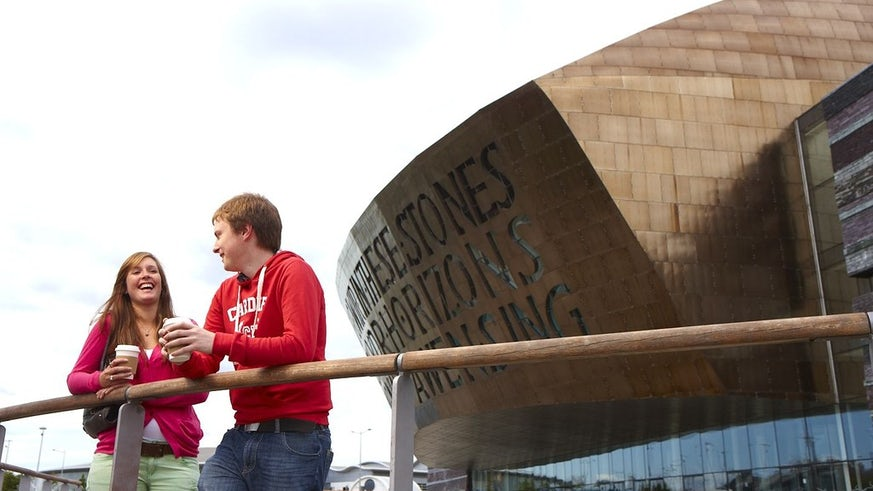 Two students in front of the Wales Millennium Centre, Cardiff Bay