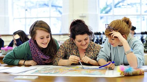 Three students looking at a map