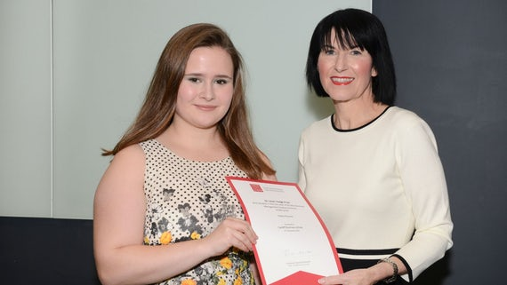 Female student collects award from Dean