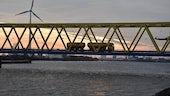 Vehicle crossing bridge at dusk