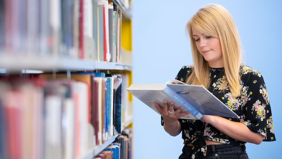 Woman student standing in the library reading a book