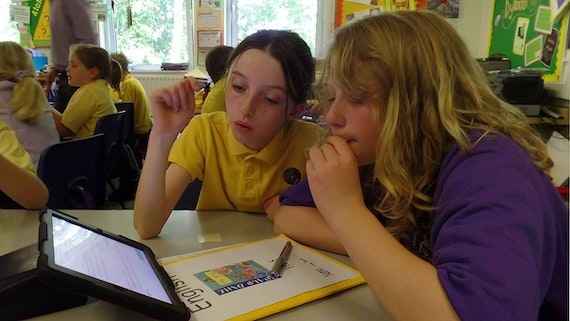 Secondary school children in a classroom using an ipad.