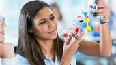 Female student using molecule models in science class