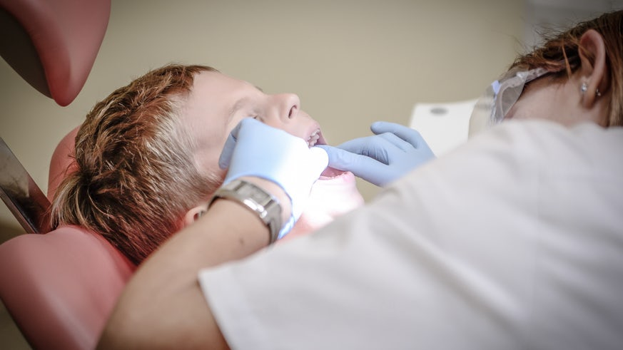 Child having teeth inspected by dentist