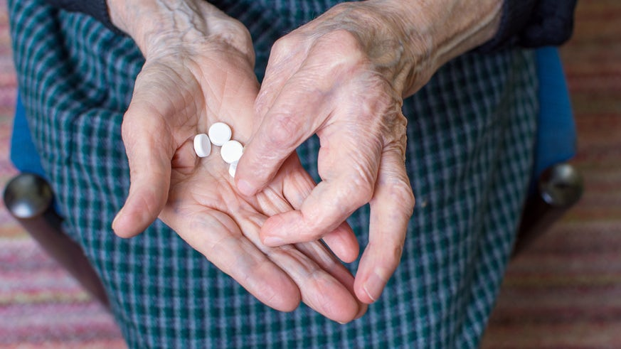 Elderly lady with pills in hand