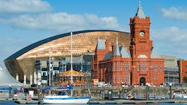 View of Cardiff Bay, with carousel and historic red-brick Pierhead Building in front of shining Millennium Centre