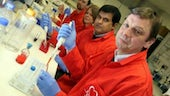 University researchers wearing red coats in lab