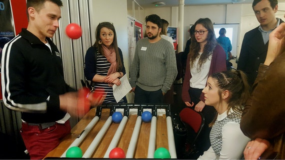 People standing around a table with tubes and plastic balls attached to it.