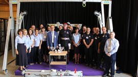 Group of people, some in medical uniform, standing looking at the camera. The Porta-Gantry machine is around and above them, and the Queen's Award bowl on a table in front of the group.