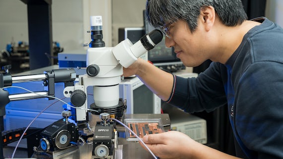 Man in Physics laboratory looking into microscope