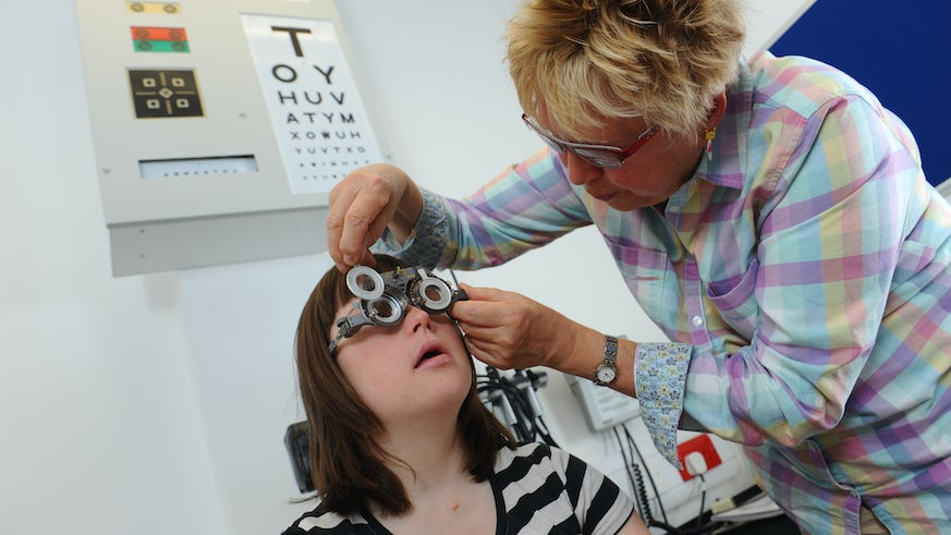 Image of Head of the clinic performing eye test on patient