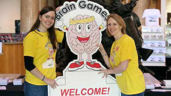Brain Games volunteers hold welcome sign