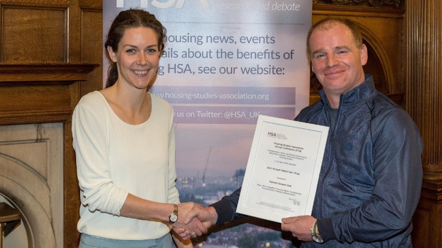 Female PhD researcher receives her best paper prize from a male representative of the Housing Studies Association