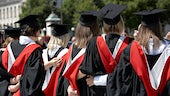 Back view of students in gowns linking arms