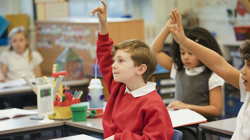 Primary school pupils with hands in the air
