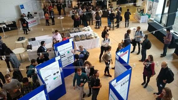 MEG researchers look at poster presentations in an atrium
