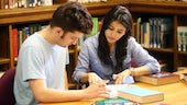 Male and female student working at table in library