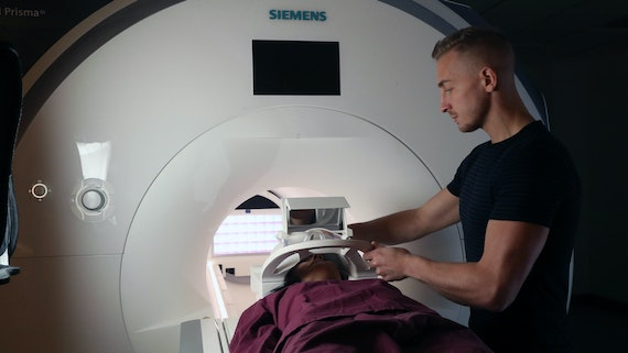 A male MRI researcher applies a headpiece to the bedof the mri scanner in which a female participant lies