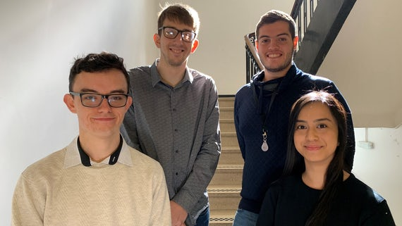 Image of one female and three male students standing on a staircase