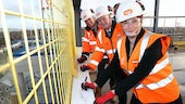 Education Minister Kirsty Williams, Bouygues UK Chief Executive Rob Bradley and Cardiff University Vice-Chancellor Professor Colin Riordan pictured 'topping out' the facility by adding their signatures to a beam on the building's highest point