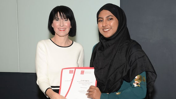 Female student collects two awards from Dean