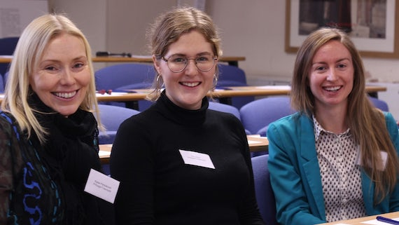 Image of three PhD students in a lecture theatre