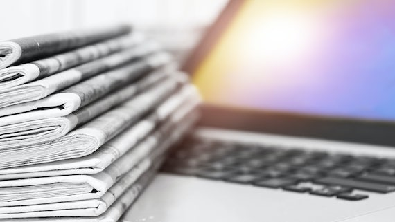 Pile of newspapers next to a laptop