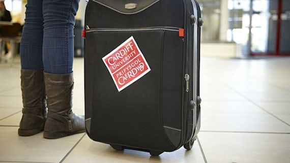 Female student's feet next to a suitcase with a Cardiff University sticker stuck to it.