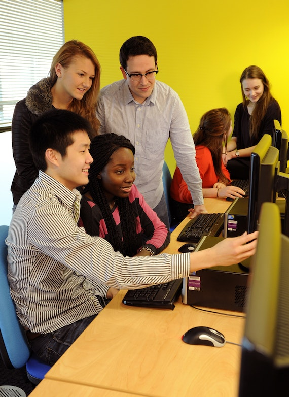Students on placement working together  around a computer
