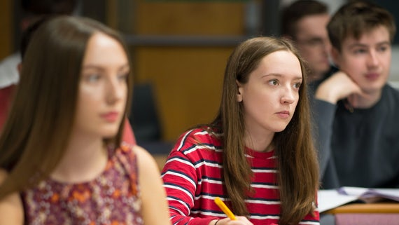 Three students sitting in a lecture hall.
