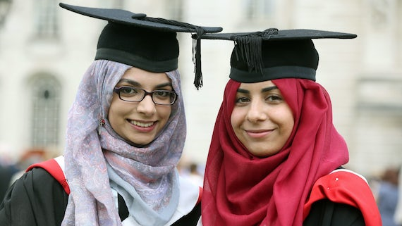 Two female graduands smiling and looking into the camera.
