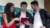 Three students standing around a tablet